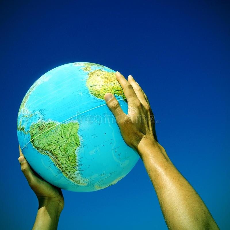 Globe. Picture of someone holding a globe in his hands over the blue sky, with a retro effect stock photography
