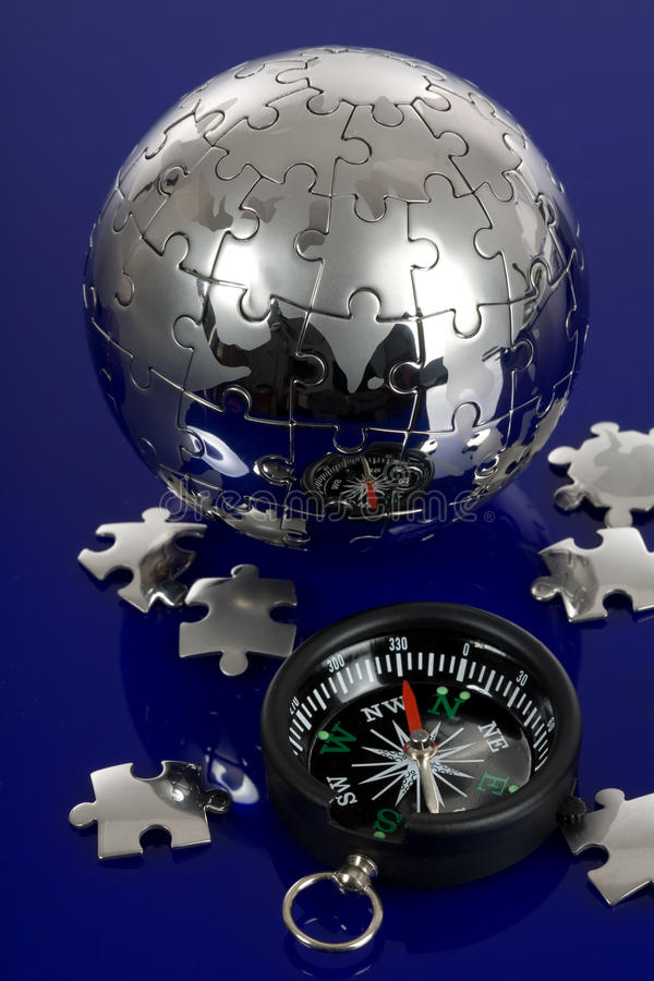 Globe puzzle with compass. On blue background royalty free stock images