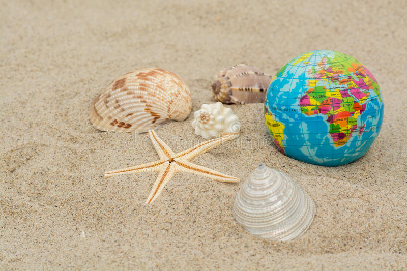 Globe with shells and starfish. On sand stock photos