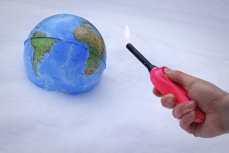 A globe in snow with a person holding a lighter with a flame, concept for global warming stock images