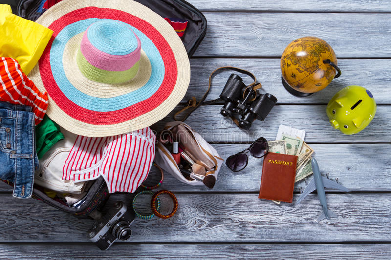 Globe and suitcase with clothes. Green piggy bank and passport. Everything is ready for travel. Woman's baggage and accessories royalty free stock photos