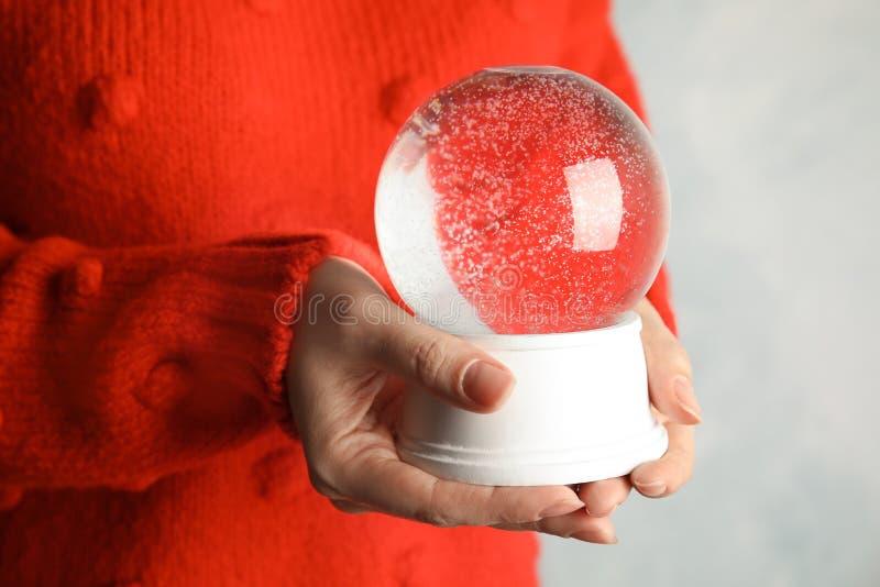 Globe vide de neige de participation de femme sur le fond clair image stock
