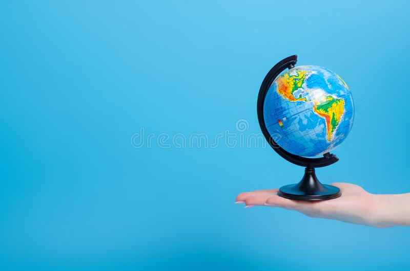 Globe world in hand. On blue background stock photography