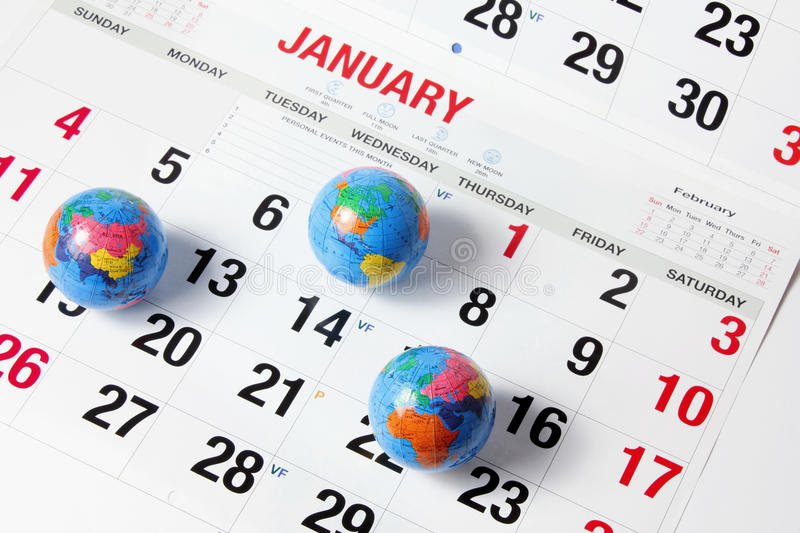 Globes on Calendar Pages. Close Up of Globes on Calendar Pages royalty free stock photography