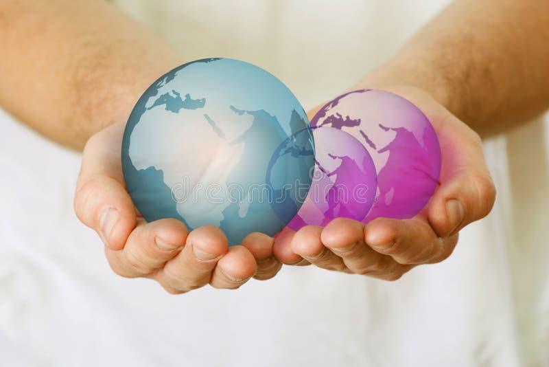 Globes dans des mains de l'homme image libre de droits