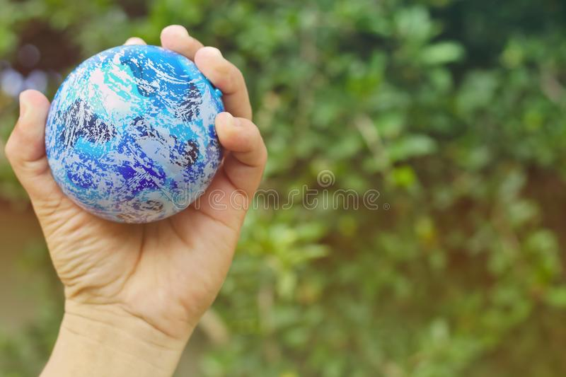 Globes in the hands of Background blurred trees free space sunlight abstract earth nature blue stock photo