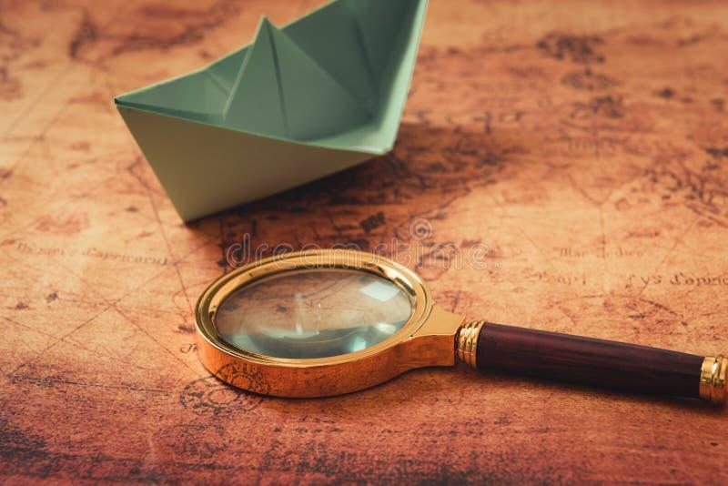 Globetrotter или путешествие исследуют концепцию, стекло увеличителя и план шлюпки бумаги на предпосылке карты мира, идее натюрмо стоковое изображение rf