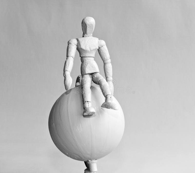 Globetrotter. Human figure situated on earth globe - mono shot royalty free stock image