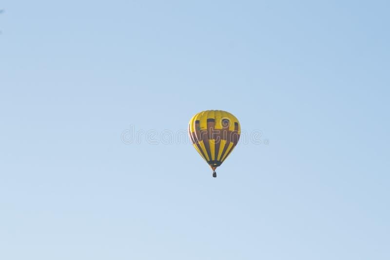 Globo amarillo contra un cielo azul aerostato Gente en la cesta Diversión Entretenimiento del verano Aventuras románticas imagenes de archivo