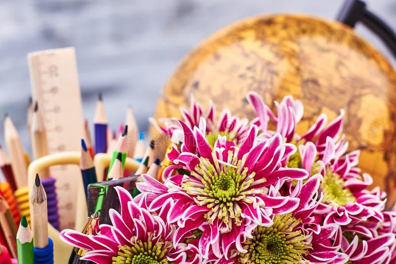 Globo, artigos de papelaria e flores do mundo fotografia de stock