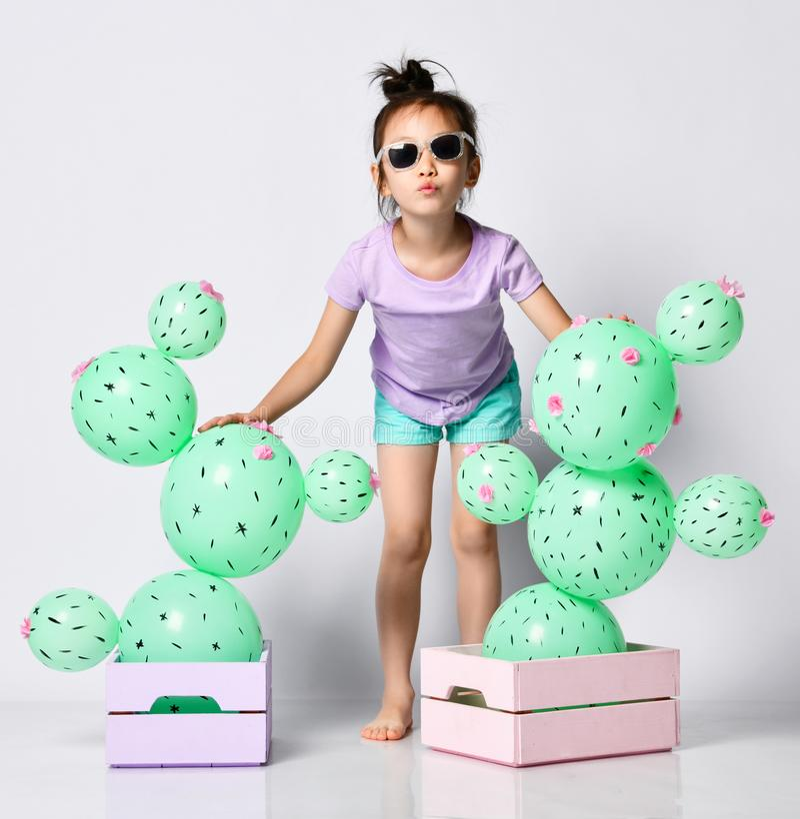 Globo asi?tico joven del cactus del control de la muchacha en la caja rosada y p?rpura en colores pastel de la flor hecha de glob foto de archivo libre de regalías
