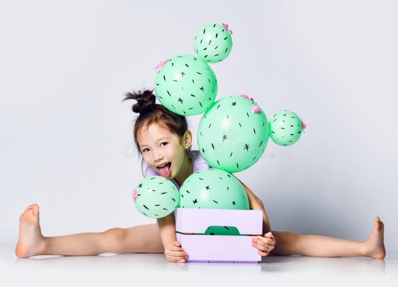 Globo asi?tico joven del cactus del control de la muchacha en la caja rosada y p?rpura en colores pastel de la flor hecha de glob fotografía de archivo libre de regalías