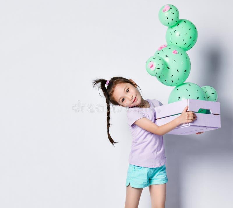 Globo asi?tico joven del cactus del control de la muchacha en la caja rosada y p?rpura en colores pastel de la flor hecha de glob fotografía de archivo