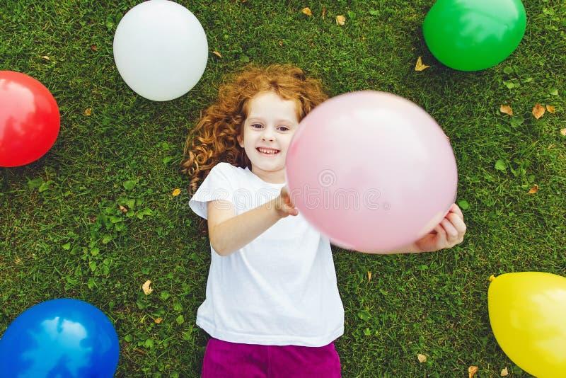 Globo coloreado tenencia feliz de la niña, mentiras en la hierba verde a fotografía de archivo