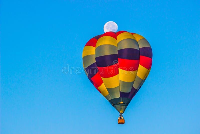 Globo colorido del aire caliente con la luna en fondo imagenes de archivo