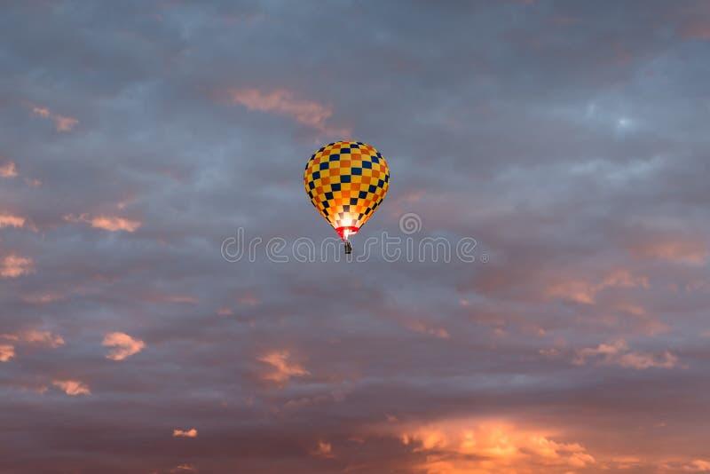 Globo colorido del aire caliente en amarillo, naranja, y los colores azul marino que brillan intensamente contra un cielo colorid fotos de archivo libres de regalías