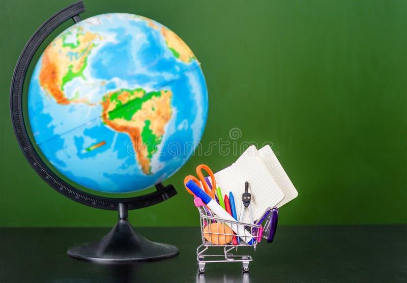 Globo com o trole pequeno da compra com artigos de papelaria perto do quadro verde vazio Espaço para o texto imagem de stock