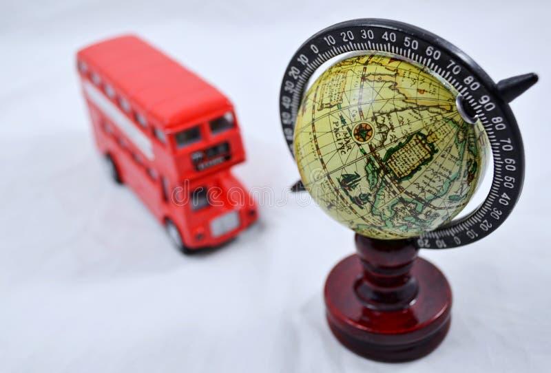 Globo com suporte de madeira e com modelo do ônibus do ônibus de dois andares no branco - viajando fotografia de stock