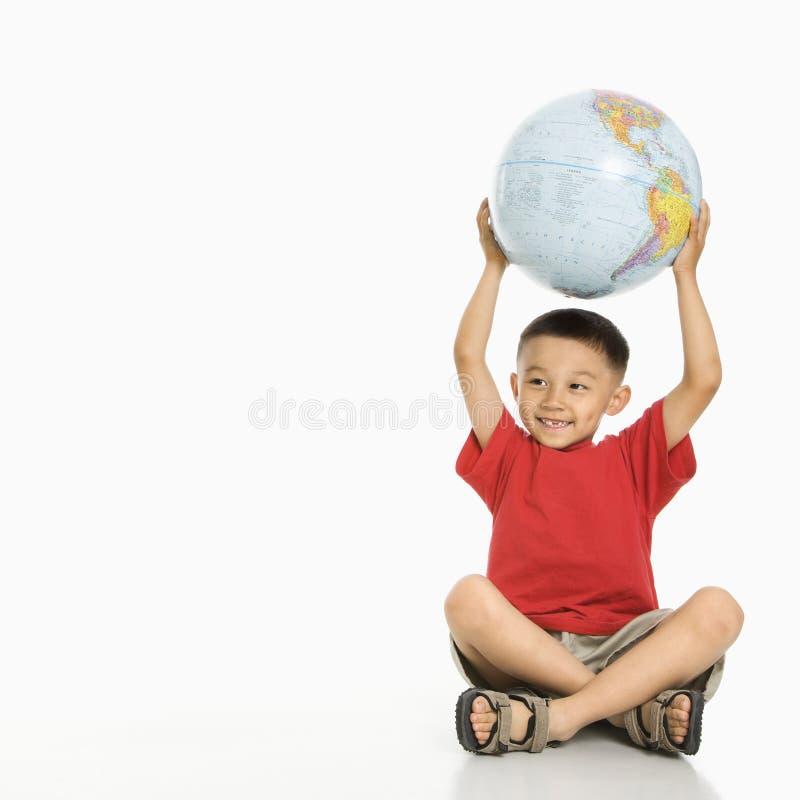 Globo da terra arrendada do menino. fotografia de stock