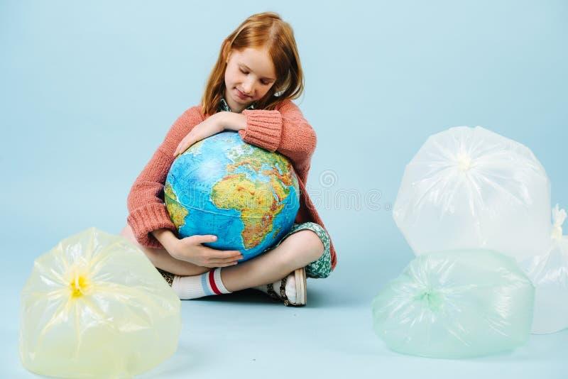 Globo da terra do planeta da terra arrendada do adolescente em seus bra?os imagens de stock