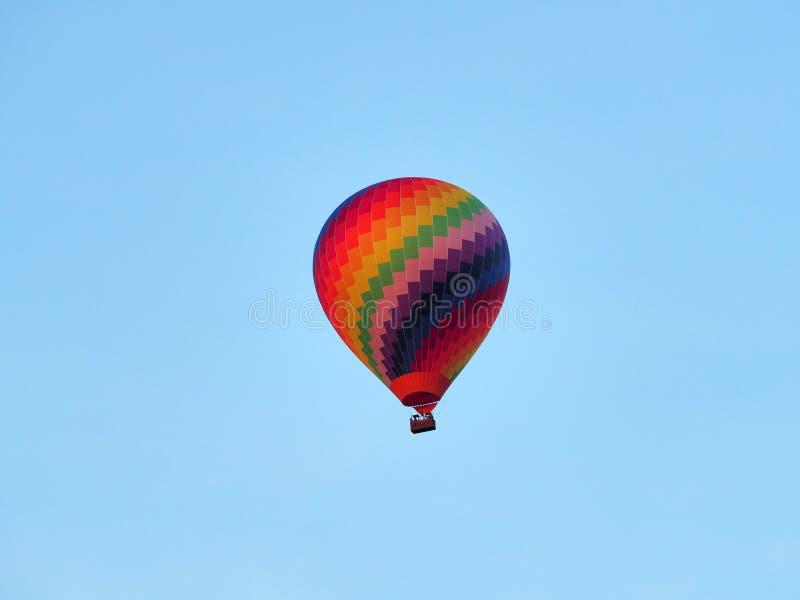 Globo de aire caliente colorido delante de un cielo azul claro imagen de archivo