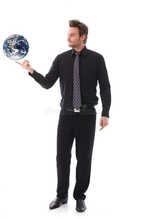 Globo de equilíbrio do homem de negócios no forefinger fotos de stock