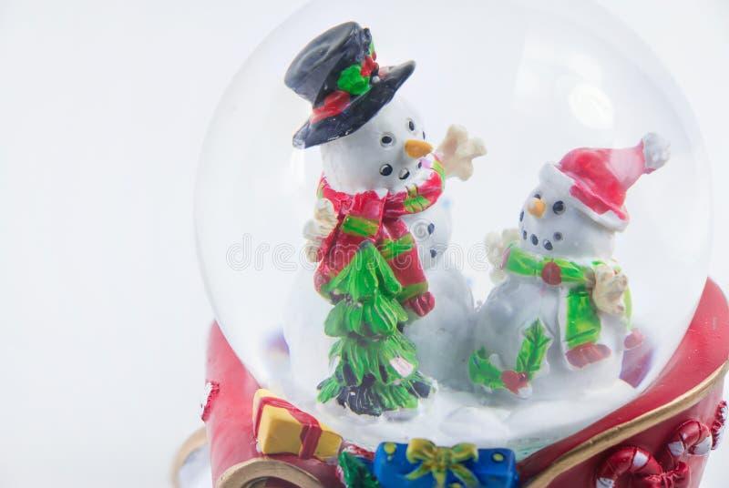 Globo de la nieve de la Navidad con el muñeco de nieve aislado en el fondo blanco fotos de archivo