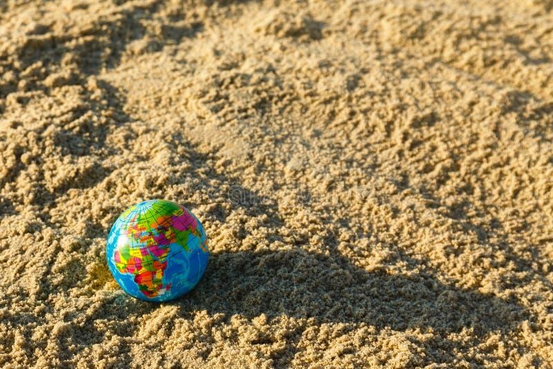 Globo de la tierra del planeta en un cierre de la playa arenosa para arriba foto de archivo libre de regalías