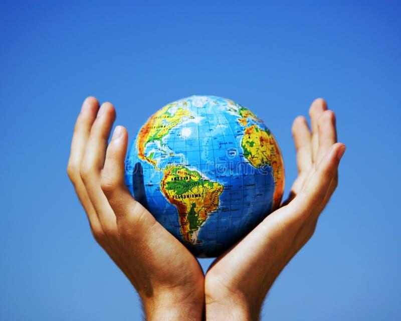 Globo de la tierra en manos. Imagen conceptual foto de archivo libre de regalías