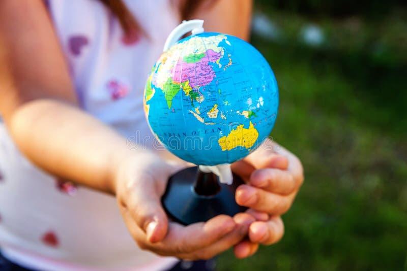 Globo de la tierra en manos de los niños foto de archivo