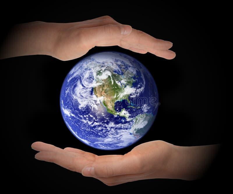 Globo de la tierra que brilla intensamente en manos en el fondo negro, concepto del ambiente, elementos de esta imagen equipados  imagen de archivo libre de regalías