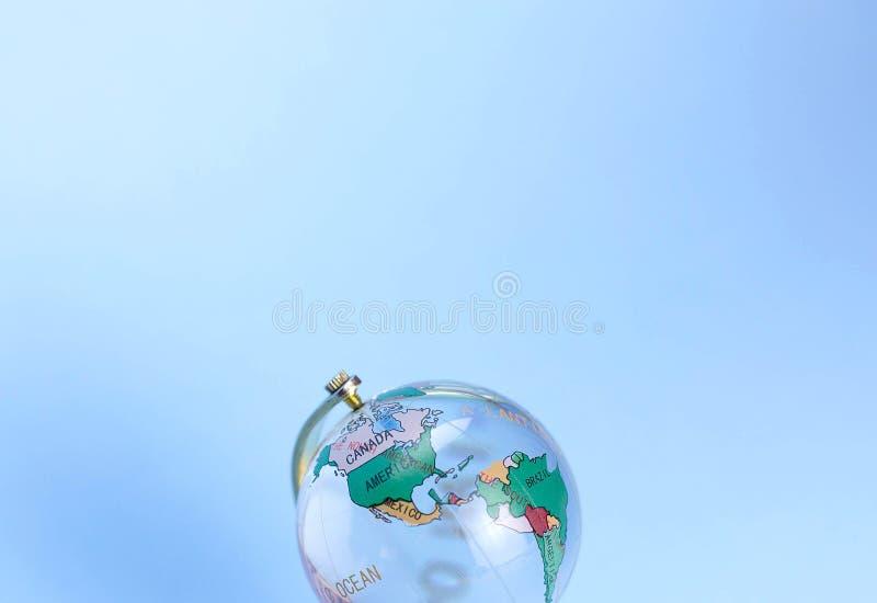 Globo de vidro com continentes marcados em um fundo azul fotos de stock