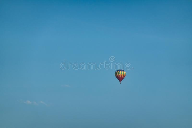 Globo del aire caliente en cielo azul imagenes de archivo