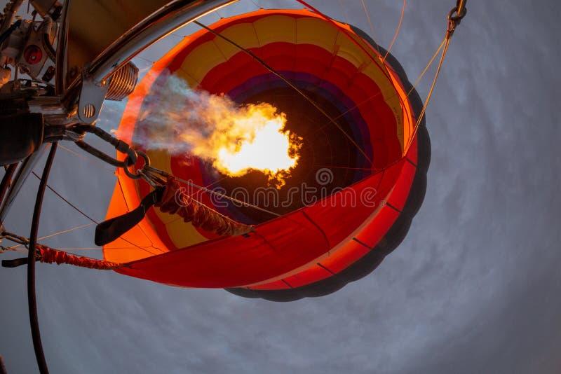 Globo del aire caliente en vuelo con la llama girada foto de archivo libre de regalías