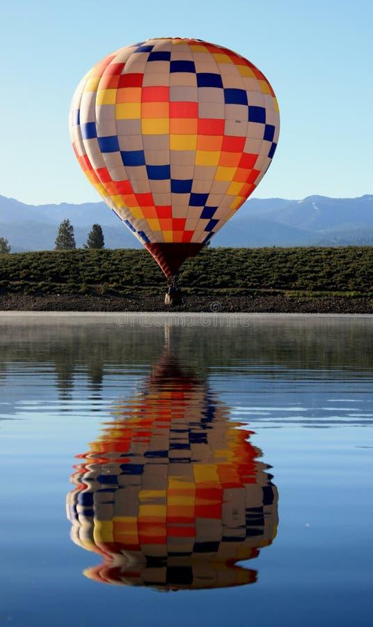 Globo del aire caliente sobre el lago imagen de archivo
