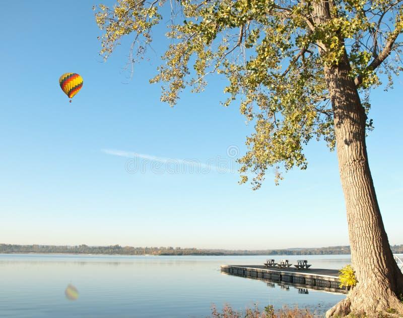 Globo del aire caliente sobre el lago fotos de archivo