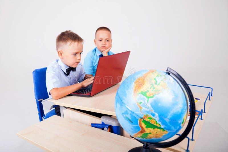 Globo del escritorio del ordenador de la escuela de dos muchachos fotografía de archivo libre de regalías