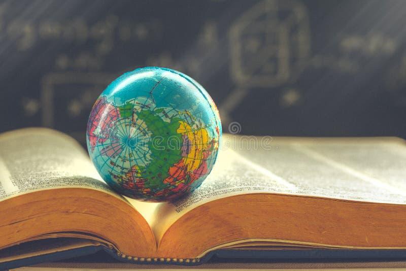 Globo del mondo sul libro Concetto della scuola di istruzione immagini stock libere da diritti
