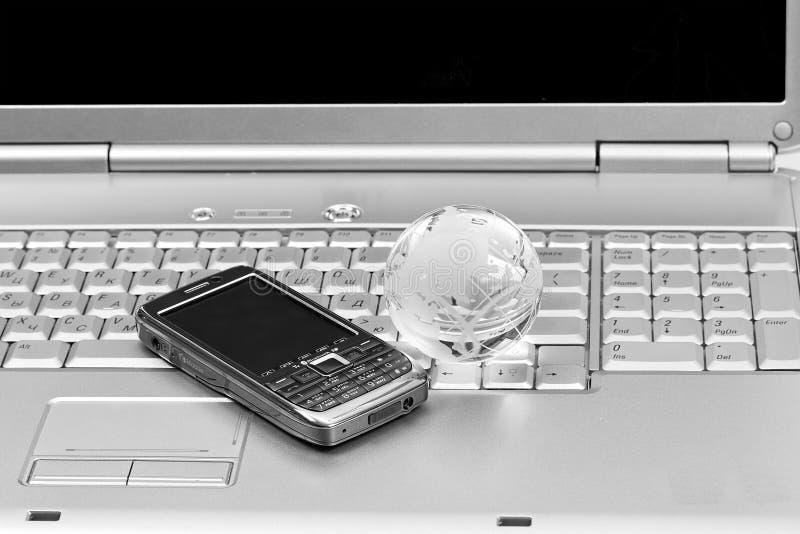 Globo del teléfono móvil y del vidrio en el teclado de la computadora portátil imagen de archivo libre de regalías
