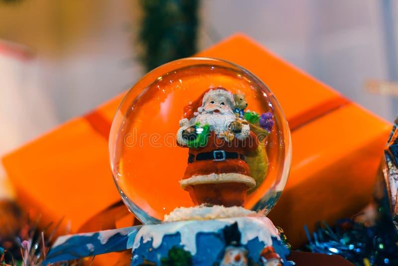 Globo della neve con il Babbo Natale dentro ed i regali di Natale nelle sedere immagini stock libere da diritti