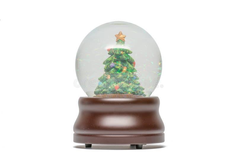 Globo della neve dell'albero di Natale verde con visibile luccicante delle scintille - base di legno marrone - isolato su bianco immagini stock libere da diritti