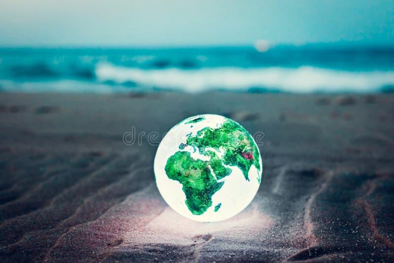 Globo della terra che emette luce sulla spiaggia alla notte fotografie stock libere da diritti