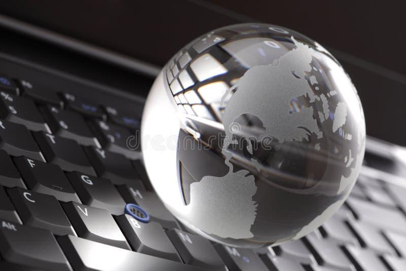 Globo di cristallo sulla tastiera del computer portatile fotografia stock