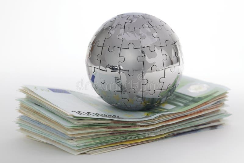 Globo di puzzle del metallo con soldi fotografie stock
