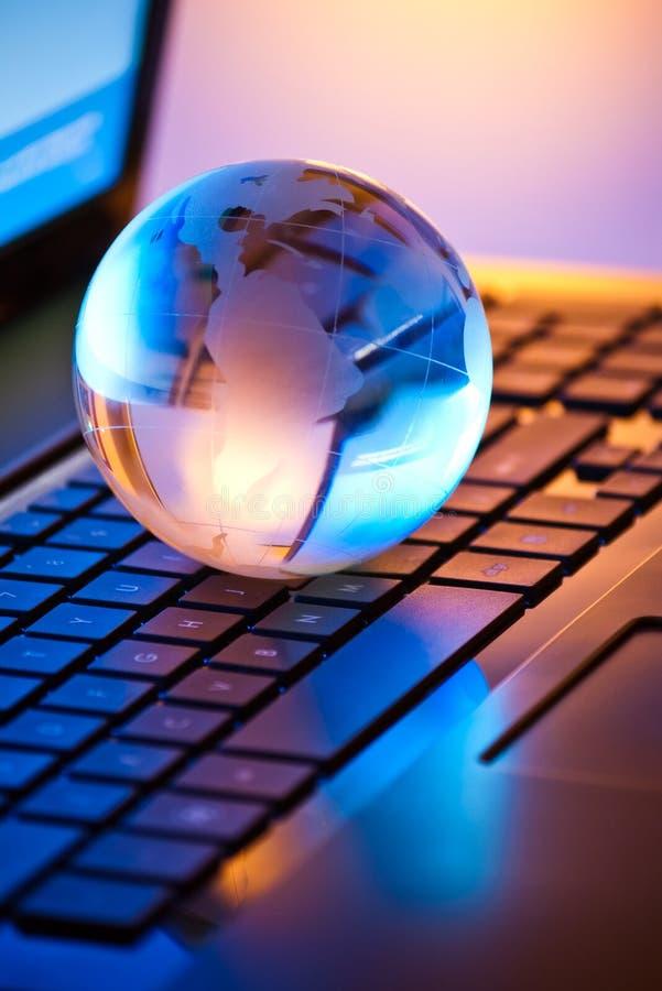 Globo di vetro sul computer portatile fotografie stock libere da diritti