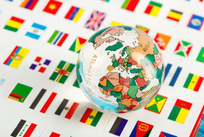 Globo di vetro sulle bandiere immagini stock