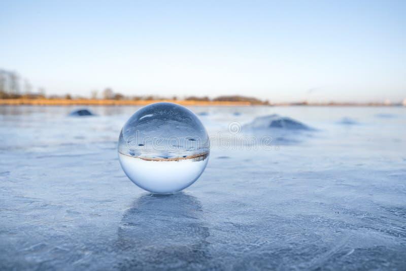 Globo di vetro trasparente su un lago congelato con ghiaccio immagini stock