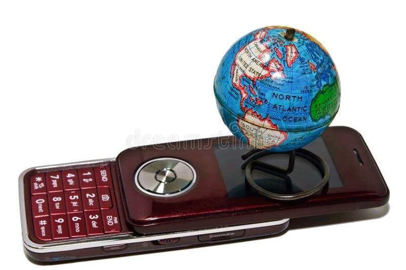 Globo do mundo e telefone de pilha pequenos imagens de stock royalty free