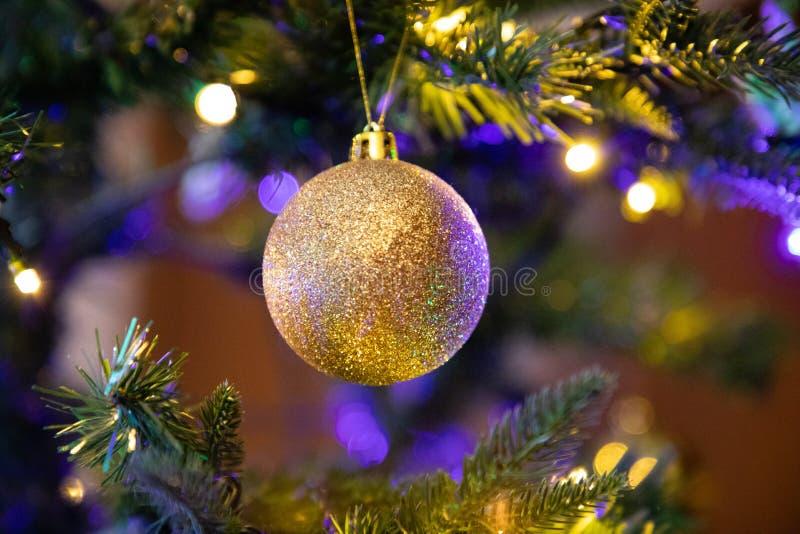 Globo dourado da decoração no fim da árvore de Natal acima imagens de stock royalty free