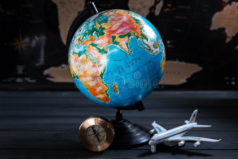 Globo geografico sui precedenti di una mappa nera con un piccolo aereo turistico fotografia stock